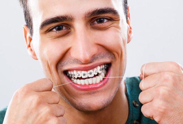 Чистка нитью зубов с брекетами