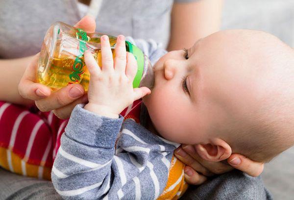 грудничок пьет сок с бутылочки