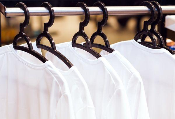 Белые рубашки на вешалках