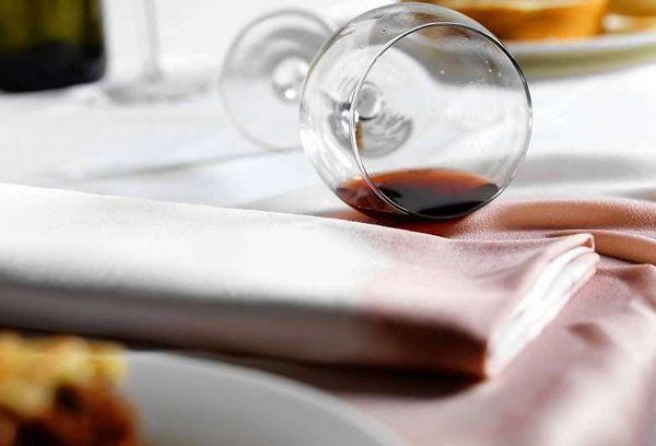 Разлитый бокал с вином на белой ткани