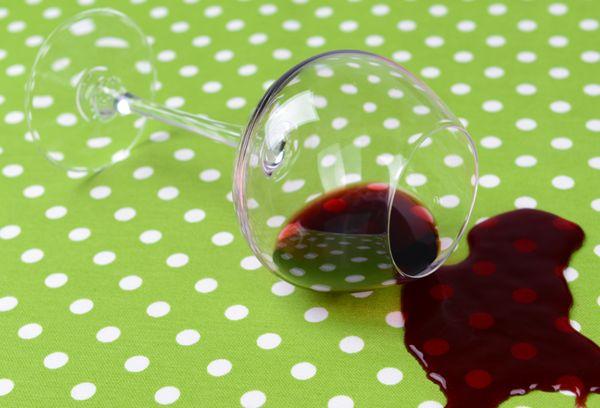 Разлитый бокал с вином на цветной ткани