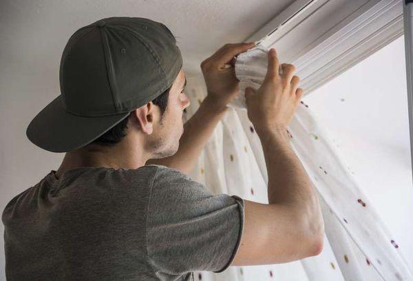 Мужчина вешает шторы