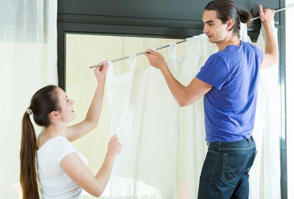 Мужчина с девушкой вешает шторы