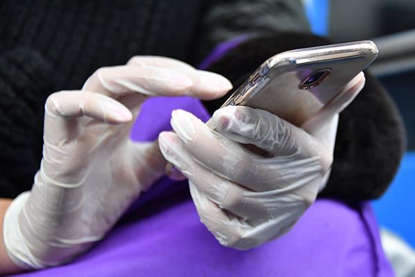 Женщина в медицинских перчатках пользуется смартфоном