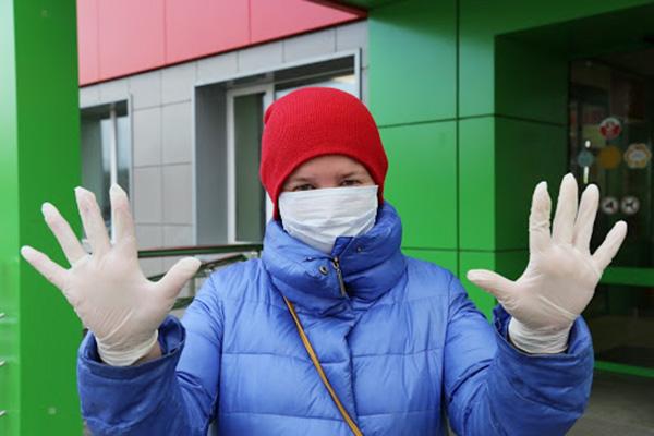 Женщина в маске и перчатках у входа в магазин