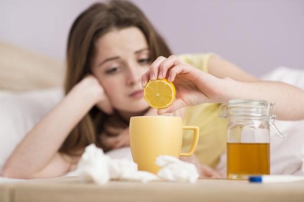 Женщина готовит воду с лимоном при простуде